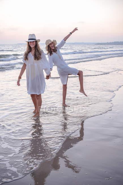 Sorridente fidanzate in abiti estivi a piedi nudi in acqua sulla spiaggia — Foto stock