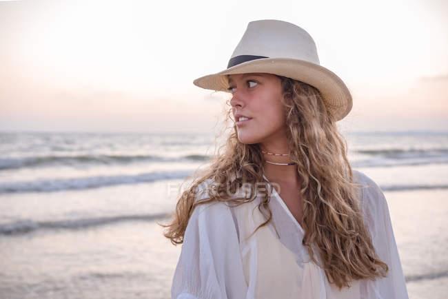 Charming woman in light white dress on wavy beach — Stock Photo