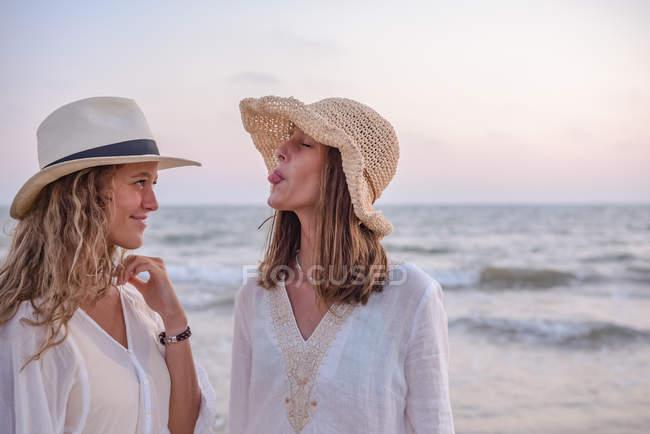 Улыбающиеся девушки в летней одежде босиком в воде на пляже — стоковое фото