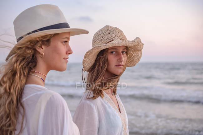Усміхнені дівчата в літньому одязі босоніж у воді на пляжі. — стокове фото