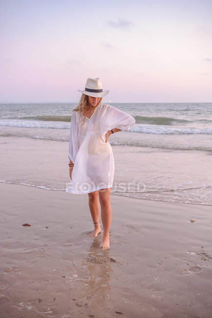 Charming woman in light white dress on wavy beach — Stock Photo