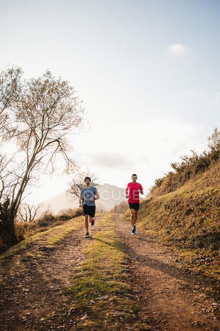Сильные активные мужчины в спортивной одежде бегут вместе по грунтовой дороге в горах в солнечный осенний день — стоковое фото