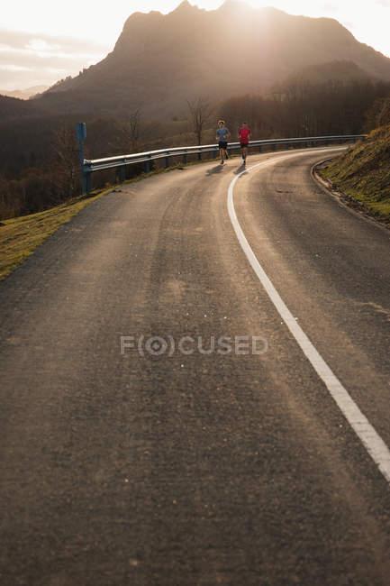 Joggers masculinos saudáveis ativos correndo juntos na estrada de asfalto curvo com luz solar de trás montanha em segundo plano — Fotografia de Stock