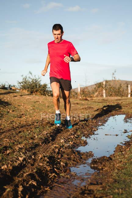 Снизу активный здоровый мужчина в красной рубашке и черных шортах бегает по средней дороге с лужей в солнечный осенний день — стоковое фото
