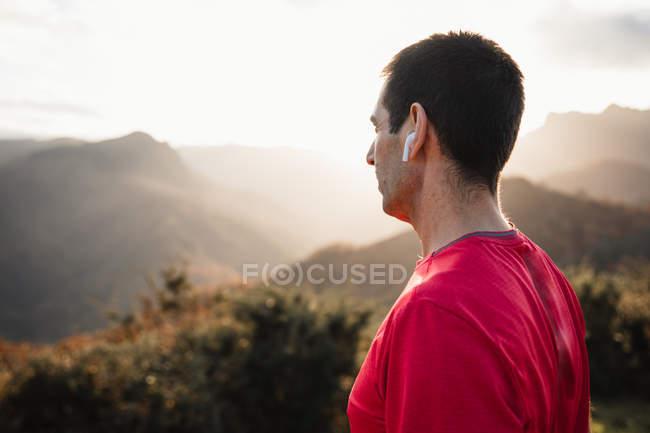 Vista laterale dell'uomo sportivo in camicie blu e rosse in piedi sulla cima di una collina verde e godendo del paesaggio mentre si rilassa dopo la corsa — Foto stock
