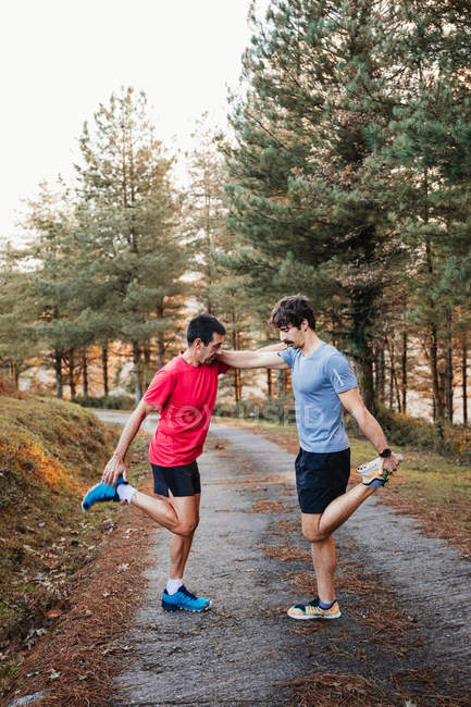 Вид сбоку уставших мужчин-бегунов в синих и красных рубашках, растягивающихся вместе после бега и напряженных тренировок — стоковое фото