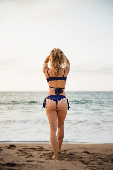 Вид сзади женщины, идущей по пляжу — стоковое фото