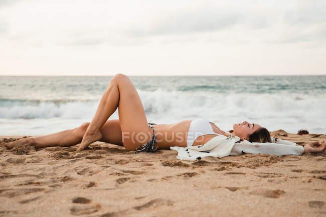 Женщина отдыхала на песчаном пляже в пасмурный день — стоковое фото