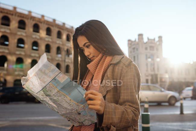 Jovem mulher asiática em roupas elegantes examinando mapa enquanto visita a cidade histórica no dia ensolarado — Fotografia de Stock