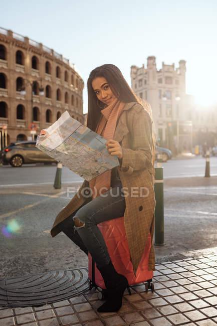 Jeune femme asiatique en vêtements élégants examinant la carte tout en visitant la ville historique le jour ensoleillé — Photo de stock