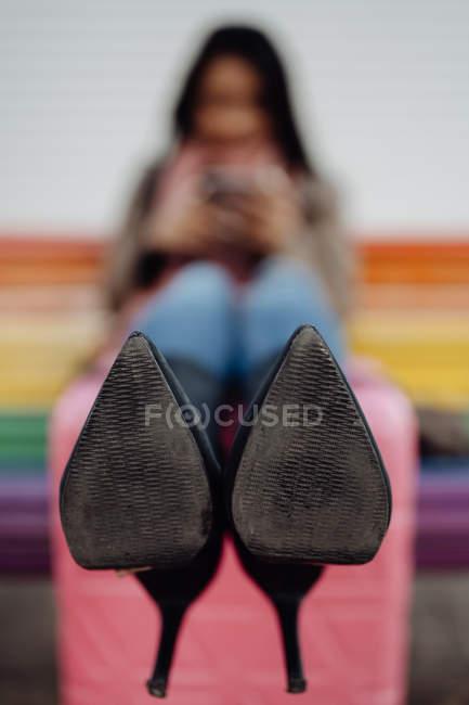 Scarpe con tacco alto di turista seduto sulla panchina e tenere le gambe sulla valigia durante il viaggio in città — Foto stock