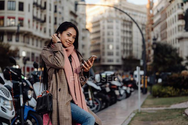 Счастливая азиатка со смартфоном улыбается и смотрит в камеру, сидя на чемодане на тротуаре на городской улице — стоковое фото