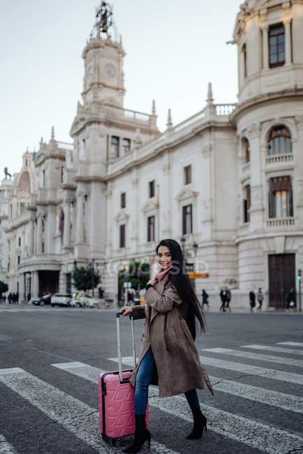 Азійка з валізою йде по дорозі перехрестям і озирається геть, відвідуючи місто в сонячний день. — стокове фото