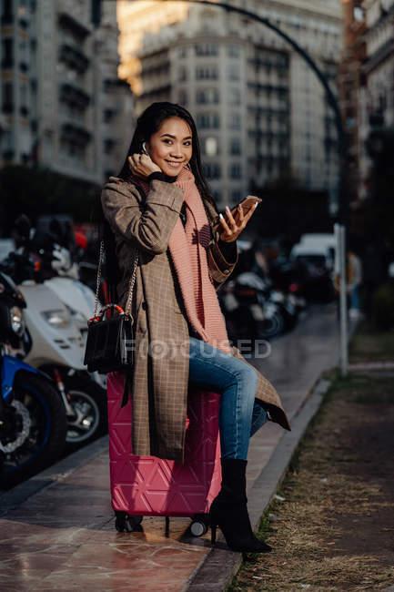 Азиатка со смартфоном улыбается и смотрит в камеру, сидя на чемодане на тротуаре на городской улице — стоковое фото