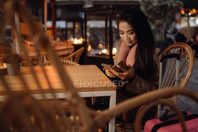 Felice donna asiatica sorridente e smartphone di navigazione mentre seduto al tavolo del ristorante vicino alla valigia in serata sulla strada della città — Foto stock