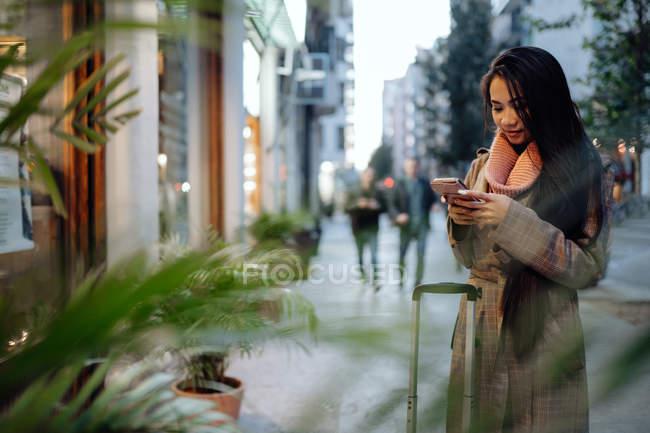 Счастливая азиатка со смартфоном улыбается с чемоданом на тротуаре на городской улице — стоковое фото