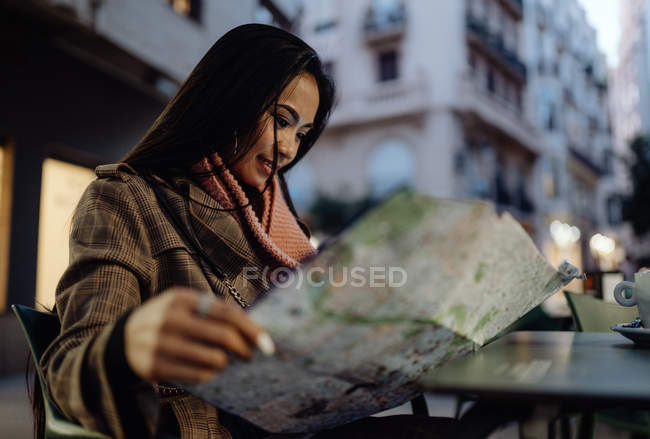 Young Asian woman smiling and reading map while sitting at table in street cafe in evening in city — Stock Photo