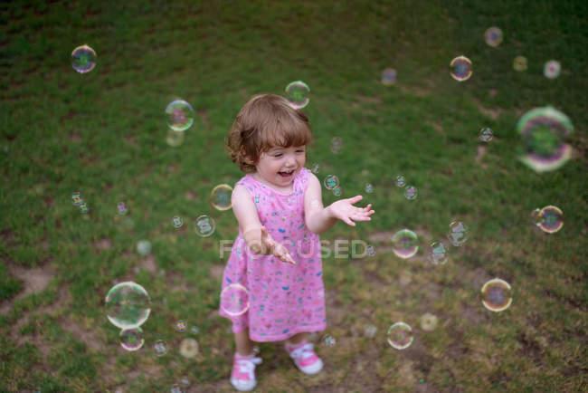 D'en haut adorable enfant en robe rose riant et capturant bulles de savon arc-en-ciel sur prairie verte dans le parc — Photo de stock