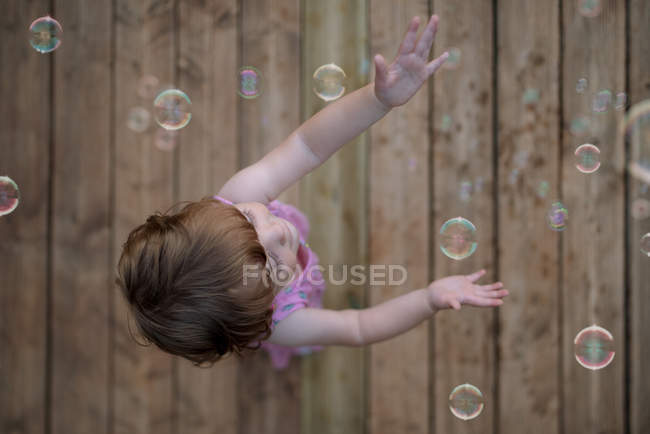 From above adorable child in pink dress laughing and capturing rainbow soap bubbles on wooden ground — Stock Photo
