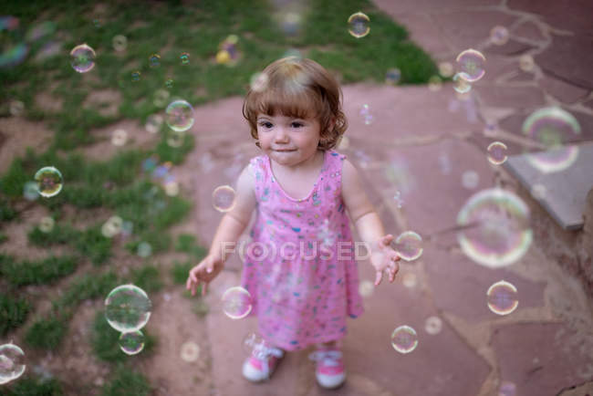 From above adorable child in pink dress laughing and capturing rainbow soap bubbles on green meadow in park — Stock Photo