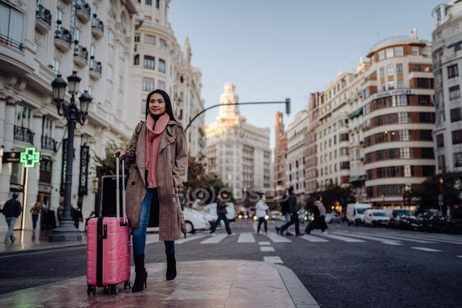 Asian woman with suitcase standing on pavement near road and looking away while visiting city on sunny day — Stock Photo