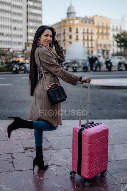 Азиатская женщина с чемоданом стоит на тротуаре возле дороги и смотрит в сторону во время посещения города в солнечный день — стоковое фото