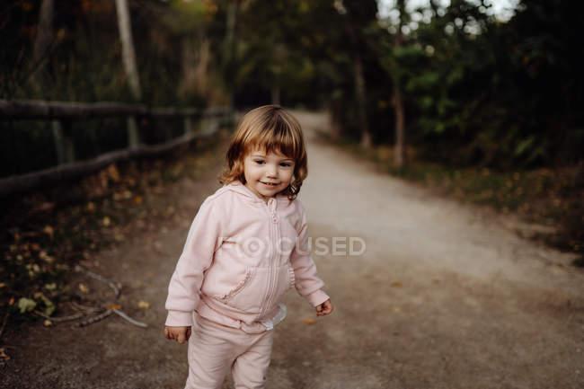 Adorable niño activo en chaqueta rosa cálido en la luz del sol en el parque - foto de stock