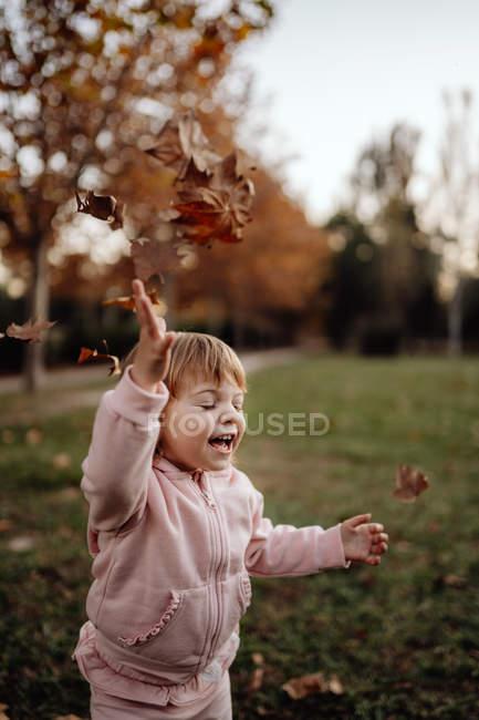 Aktives spielerisches Kind in rosa warmer Kleidung mit geschlossenen Augen vor Vergnügen, das Herbstlaub auf der Wiese im Park wirft — Stockfoto