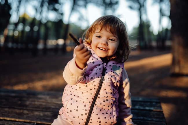 Adorabile bambino attivo in caldo bastone giacca rosa e mostrando alla fotocamera alla luce del sole nel parco — Foto stock