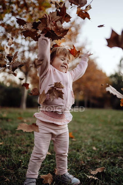 Active playful kid in pink warm clothes with closed eyes from pleasure throwing up autumn leaves in meadow in park — Stock Photo