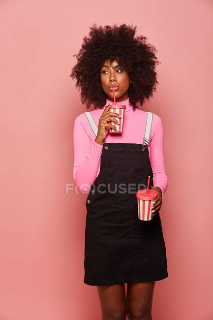 Happy black woman with disposable cup of drink standing against pink background — Stock Photo