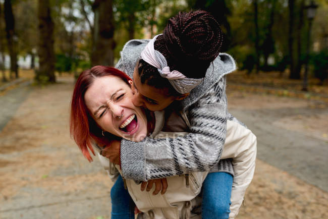 Stylish excited couple multiethnic of young lovely girlfriends having fun together piggybacking in park in sunny day — Photo de stock