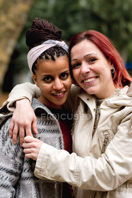 Stylish lovely multiethnic couple of smiling women embracing and looking at camera in park — Stock Photo