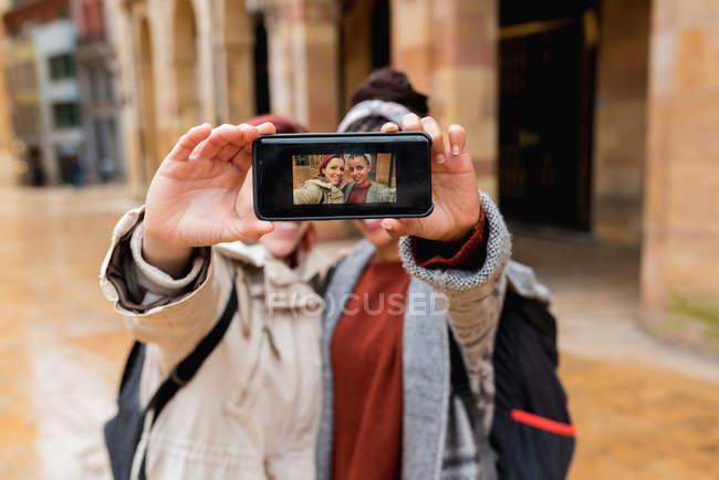 Femmes multiethniques joyeuses équilibrées prenant selfie sur téléphone portable et montrant la photo à la caméra dans la rue — Photo de stock