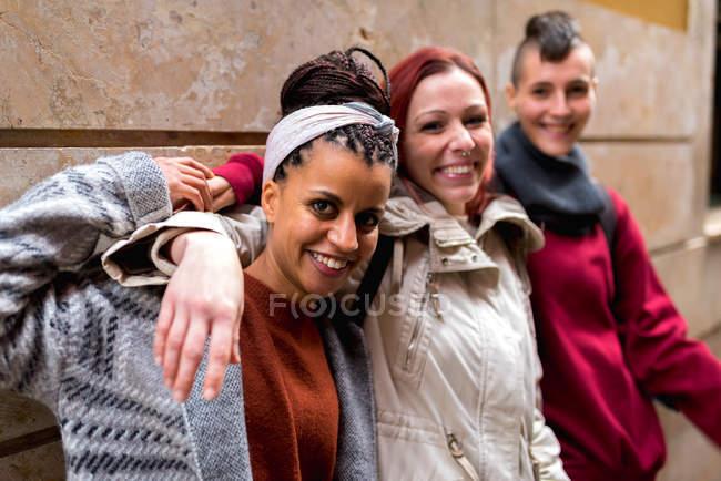 Amigos multirraciais elegantes em pé na rua e olhando para a câmera — Fotografia de Stock