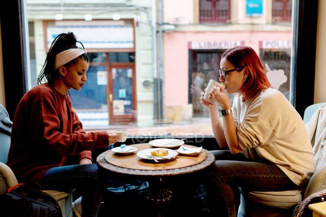 Vista laterale di eleganti entusiasta multietnico ragazza amici parlare e bere seduto al tavolo finestra nelle vicinanze in caffè — Foto stock