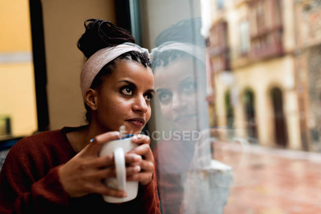 Thoughtful charming African American woman leaning on glass window drinking coffee and dreamily looking away — Stock Photo