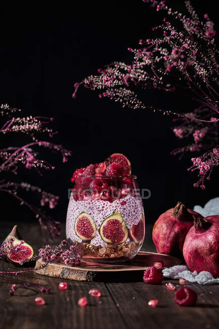 Chia pudding with fresh figs and raspberries including pomegranate and cream in glass at table among pink blossom bunches on black background — Stock Photo