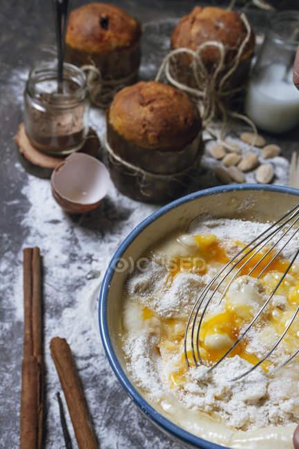 Batir los productos de mezcla en un tazón de cerámica mientras se prepara la masa para el típico pastel de panettone de Navidad en la mesa - foto de stock