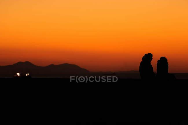Loving couple standing below sunset sky — Stock Photo