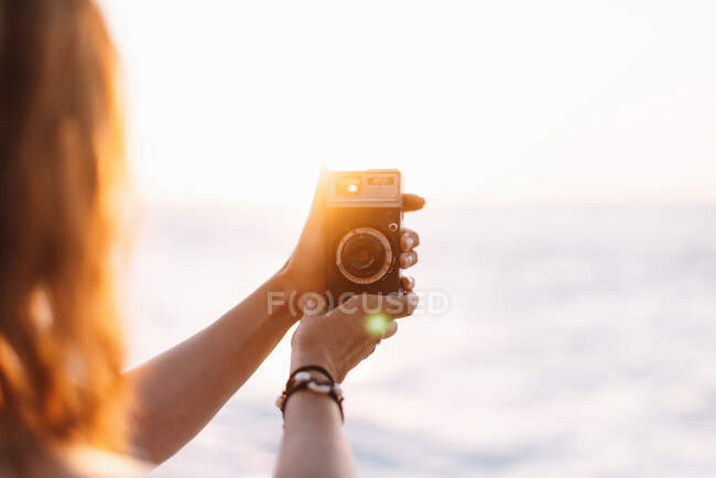 Female photographer taking picture with camera — Stock Photo