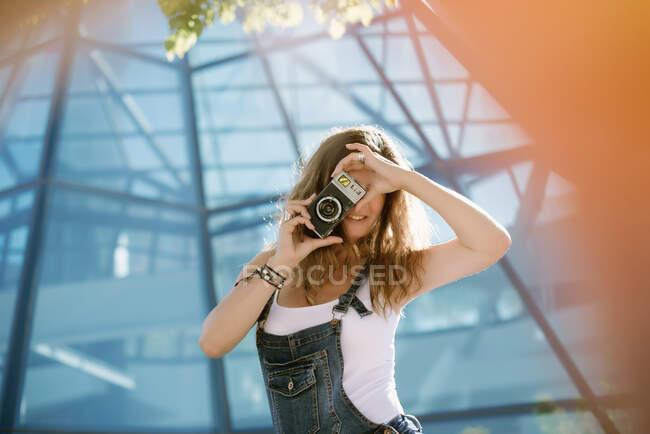 Mujer joven tomando fotos con la cámara en la ciudad - foto de stock