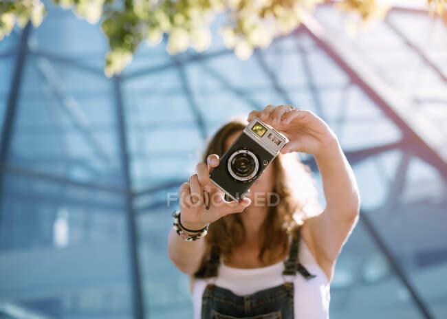 Mulher tirando foto com câmera — Fotografia de Stock