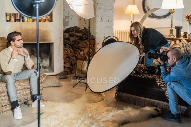 Professional photographer shooting stylish man against interior of cozy country house — Stock Photo