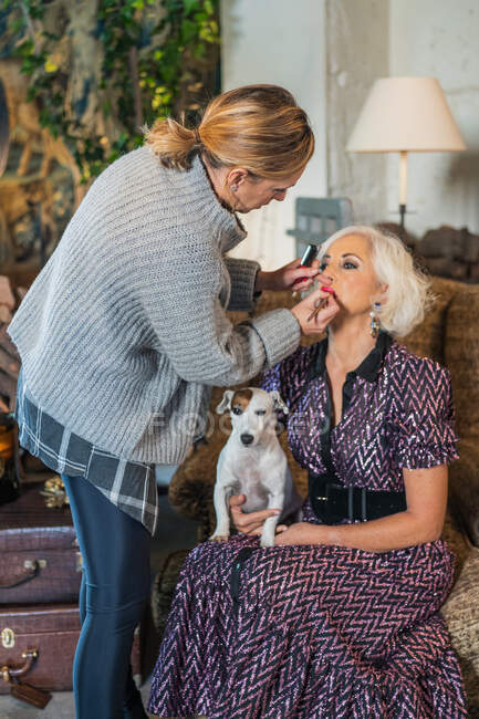 Makeup artist applying makeup on model with obedient pet before shooting with camera — Stockfoto