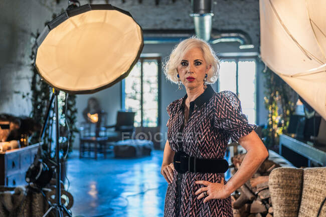 Pensive gray haired actress in elegant sitting beside soft box and looking at camera during break in work against blurred interior of cozy contemporary studio — Stock Photo