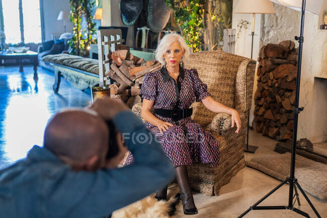 Focused man shooting with camera senior confident woman against country house interior — Stockfoto