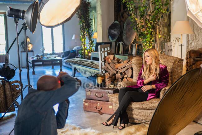 Fotógrafo profissional atirando com câmera sensual mulher confiante no interior da casa de campo acolhedora — Fotografia de Stock