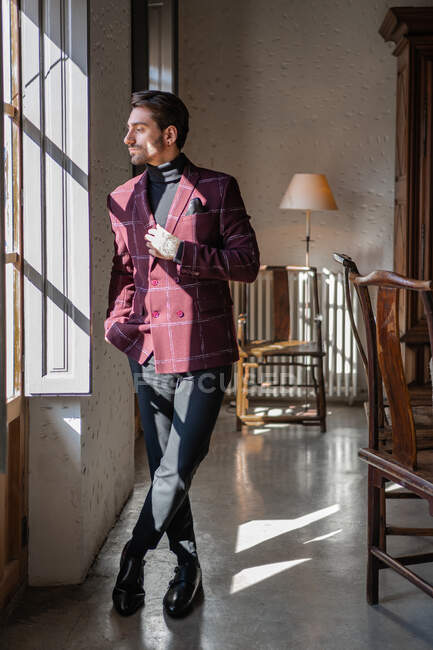 Serious confident elegant man looking out window in country house — Stock Photo