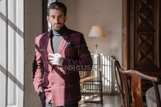 Serious confident elegant man looking at camera in country house — Stock Photo